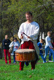 Musician in historical costumes performs in a park. He plays drums. Royalty Free Stock Photography