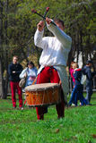 Musician in historical costumes performs in a park. He plays drums. Royalty Free Stock Image