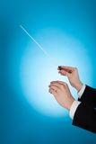 Musician Holding Baton Against Blue Background Royalty Free Stock Photography