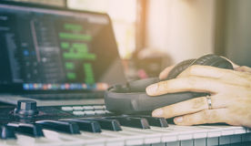 Musician holding Headphone on music keyboard Royalty Free Stock Images