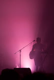 Musician illuminated in silhouette on stage Stock Photography