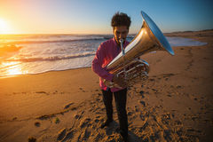 Musician instrumentalist playing the Tuba on the sea coast. Hobby. Royalty Free Stock Image