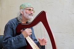 Old musician playing harp. Musician Jiri Wehle playing harp outside the castle Rostejn, Czech Republic Stock Images