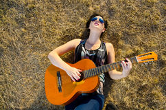 Musician laying on grass Stock Photo