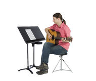Musician looking at music notation and playing Stock Images