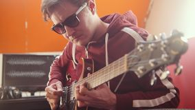 A musician man in headphones and glasses playing guitar and recording the melody in the studio. Mid shot