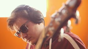 A musician man in headphones and glasses playing guitar and recording the sound in the studio. Mid shot