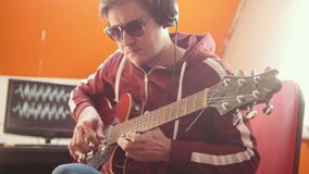 A musician man in headphones playing guitar and recording the sound in the studio. Mid shot