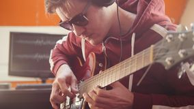 A musician man in headphones playing guitar in the studio. Mid shot