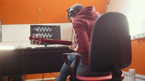 A musician man in headphones sitting by the computer in the studio and recording a song. Mid shot