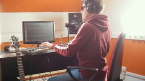 A musician man playing on a MIDI-keyboard and recording it for a track. Mid shot