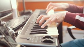 A musician man playing on a MIDI-keyboard in the sound studio. Mid shot
