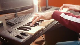 A musician man playing music on a MIDI-keyboard in the sound studio. Mid shot