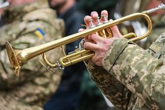 Musician military band of the Ukrainian army plays the trumpet on the march, stock photos