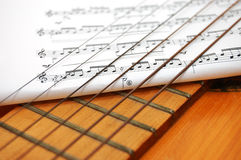Musician notes under guitar's strings Stock Photos
