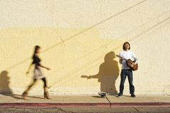 Musician On Sidewalk And Woman Pedestrian Royalty Free Stock Photography
