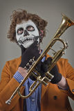 Musician Painted Face. Thinking trumpet player with face painted as human skull royalty free stock photography