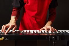 Musician play the keys of the electronic synth on black background Royalty Free Stock Photo