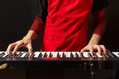 Musician play the keys of the synth on black background Stock Photo
