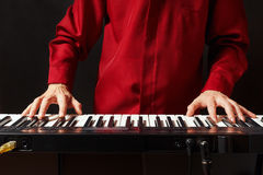 Musician play the keys of the synthesizer on black background Stock Image