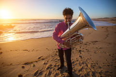 Musician play to musical instrument Tuba on ocean shore. Hobby. Royalty Free Stock Photography