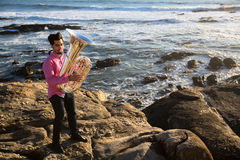 Musician play to musical instrument Tuba on romantic rocky sea shore. Hobby. Royalty Free Stock Photography