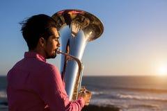 Musician play to Tuba on romantic sea shore. Concert. Stock Photos