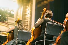 Musician play violin. Female violinist playing the violin stringst on the concert stage. Closeup.  Royalty Free Stock Photography