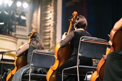 Musician play violin. Female violinist playing the violin stringst on the concert stage. Closeup.  Stock Image