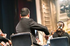 Musician play violin. Violinist playing the violin stringst on the concert stage. Closeup.  Stock Photography