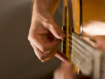 Musician playing acoustic guitar. Close up on a man`s hand playing classical acoustic guitar Stock Photos