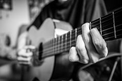 Musician playing acoustic guitar. Black and white photo royalty free stock image