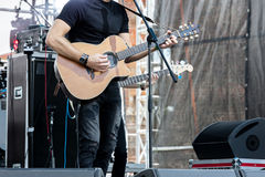 Musician playing acoustic guitar on outdoor stage during live co Stock Photography