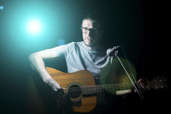 Musician playing acoustic guitar and singing Stock Image