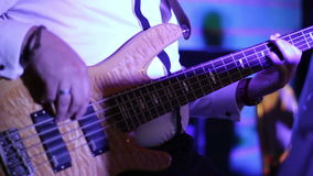 Musician playing bass guitar in a disco lights stock video