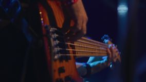 Musician playing bass guitar on stage during performance. Medium shot of musician playing bass guitar on stage during performance stock footage