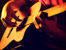 Musician playing classic guitar on a stage Stock Image