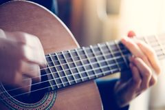Musician is playing a classical guitar, fretboard and fingers. Musician plays a classical guitar, blurry hands, fretboard and fingers instrument playing stock photography
