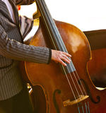 Musician playing contrabass. Musician playing yellow retro contrabass Royalty Free Stock Image