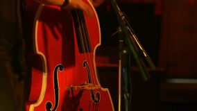 Musician playing contrabass. Musician playing red contrabass at stage stock footage