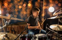Musician playing drum kit at concert over lights. Music, people, musical instruments and entertainment concept - male musician or drummer with drumsticks playing Stock Photos