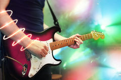 Musician playing electric guitar. On a scene, glowing line round hand Stock Photography