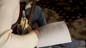 Musician playing electric guitar and looking at paper with printed song words lying on his knee. Man guitarist in stock photography