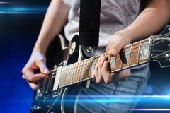 Musician playing electric guitar with mediator. Music, people, musical instruments and entertainment concept - close up female musician hands playing electric Royalty Free Stock Photography