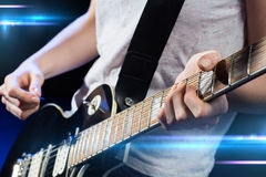 Musician playing electric guitar with mediator. Music, people, musical instruments and entertainment concept - close up female musician hands playing electric Royalty Free Stock Photos