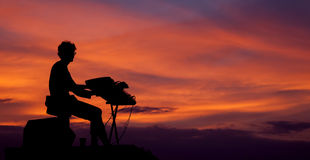 Musician playing the electric piano on the sunset Royalty Free Stock Photos