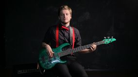 Musician playing electrical bass giutar. On dark background stock footage