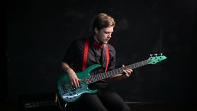 Musician playing electrical bass guitar. On dark background stock footage
