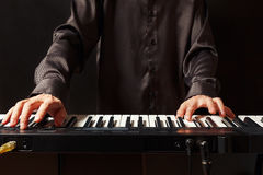 Musician playing the electronic synth on black background Stock Photos
