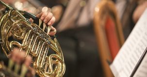 Musician playing French horn during concert. Lockdown shot of musician playing French horn. Male is using brass instrument during a concert. He is wearing tuxedo stock footage